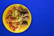 canvas print picture -  fried liver with potatoes and stewed tomatoes top view. fried liver on a yellow plate on a blue background