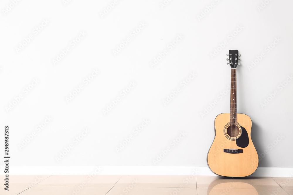 Nowoczesna gitara akustyczna w pobliżu białej ściany <span>plik: #298987313 | autor: Pixel-Shot</span>