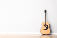 Modern Acoustic Guitar Near White Wall