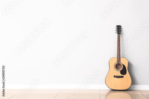 Obraz Modern acoustic guitar near white wall - fototapety do salonu