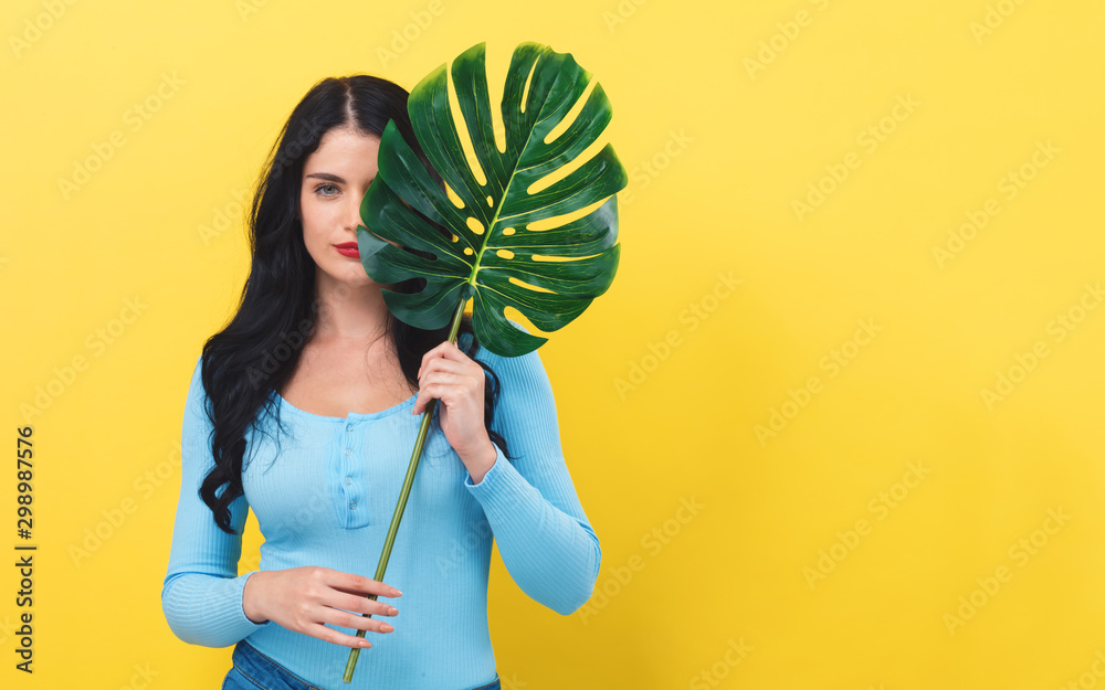 Fototapety, obrazy: Young woman with a trendy tropical leaf on a yellow background