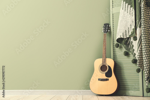 Modern acoustic guitar and folding screen near color wall - 298987772