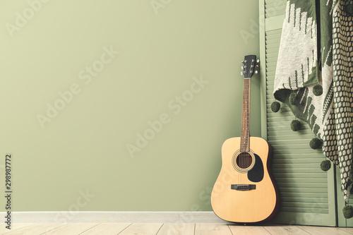 Fotografía  Modern acoustic guitar and folding screen near color wall