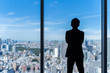 businessman wearing suit looking cityscape of tokyo