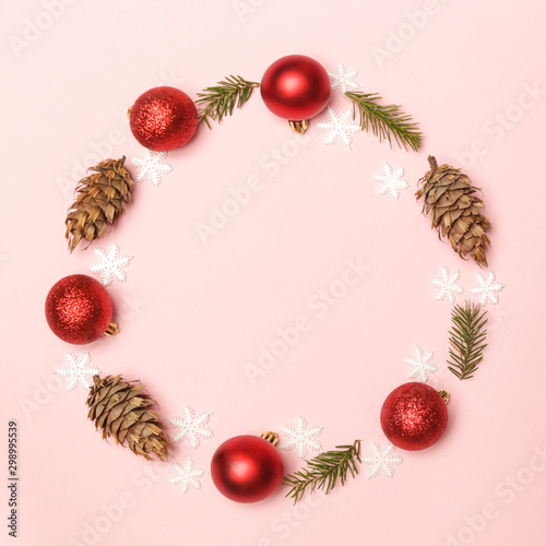 Red Christmas shiny balls and fir twigs on pale pink background. Christmas ornaments arrangement with copy space.