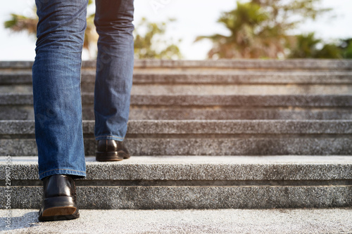 Fotografie, Obraz  Close up legs shoes of young business man One person walking stepping going up the stairs in modern city, go up, success, grow up