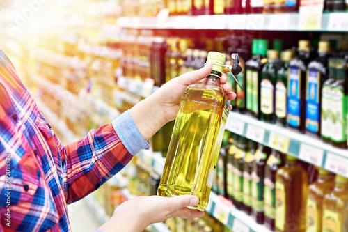 Fototapeta Buyer with sunflower oil in shop obraz