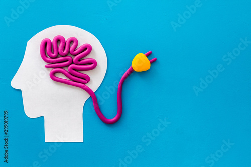 Obraz Brain charging and mental rest. Plug and cable leads to plastiline meanders on blue background top view space for text - fototapety do salonu