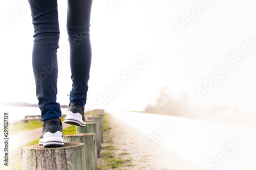 Fototapeta A woman walking on stump carefully next to the road. Concept of living life with confidence and take care every steps of moving forward to make sure life safe. Free copied space for text on right. obraz