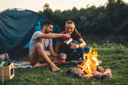 Fotografering romantic couple on camping by the river outdoors