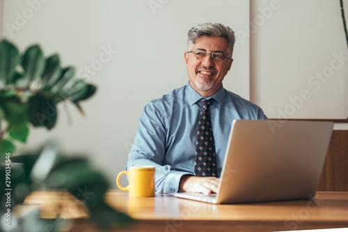 Fotomural  handsome businessman sitting desk in his office