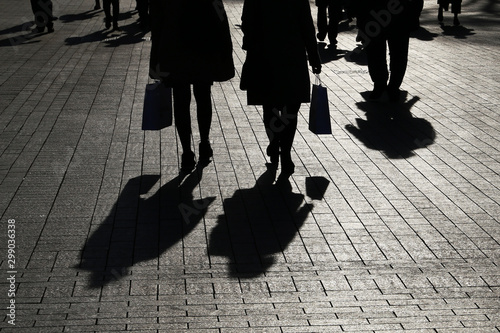 plakat Silhouettes and shadows of people on the street, couple of women in the foreground. Crowd walking on sidewalk, concept of social issues, population and society
