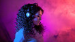 canvas print picture - Portrait of a curly pensive sensual woman in big headphones, with a soft smile listening to music, on neon background.