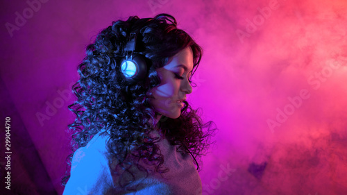 Portrait of a curly pensive sensual woman in big headphones, with a soft smile listening to music, on neon background. - 299044710
