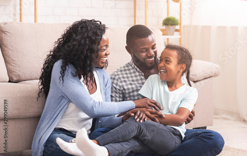 Pinturas sobre lienzo  Black parents tickling their daughter and laughing together at home
