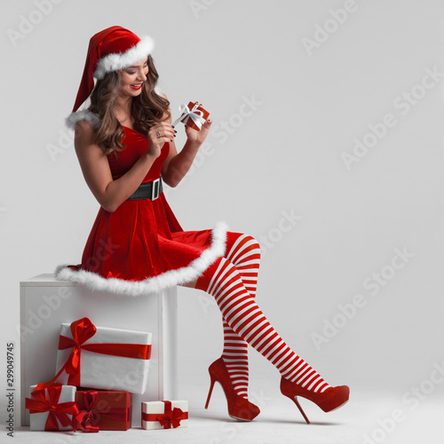 Valokuva  Girl in santa dress unwrapping gift
