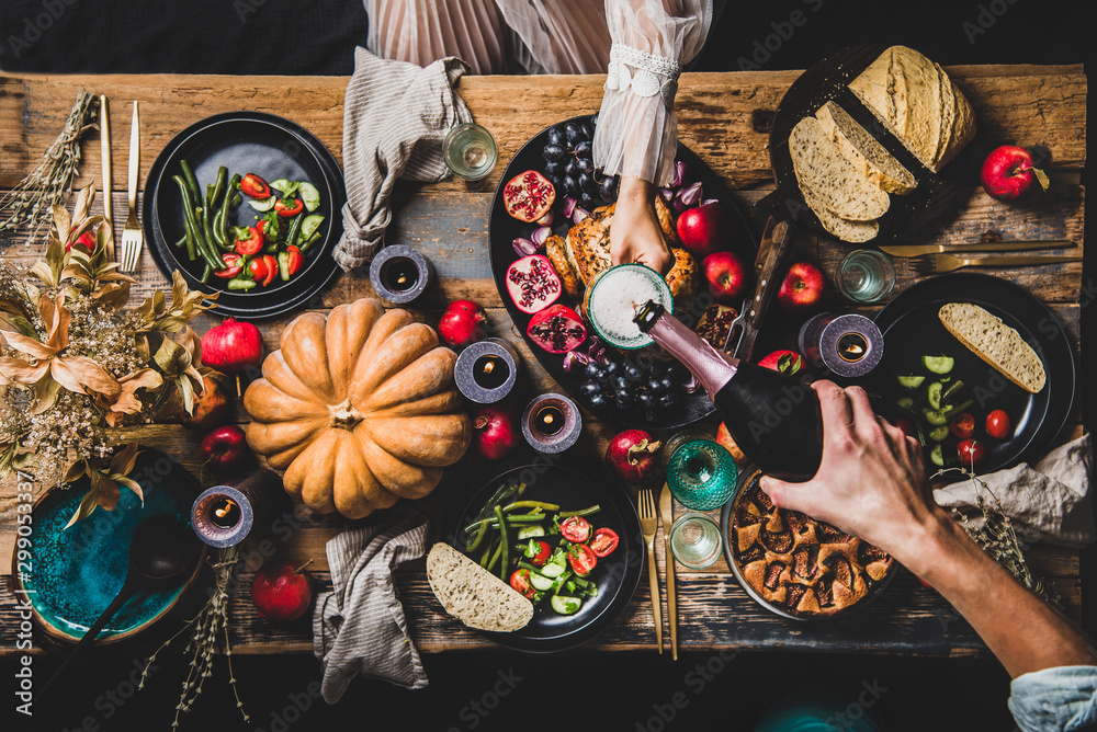 Fototapety, obrazy: Thanksgiving table setting for family gathering. Flat-lay of man pouring champagne to glass at festive table with roasted chicken, vegetables, fig pie, fruit, candles over wooden background, top view