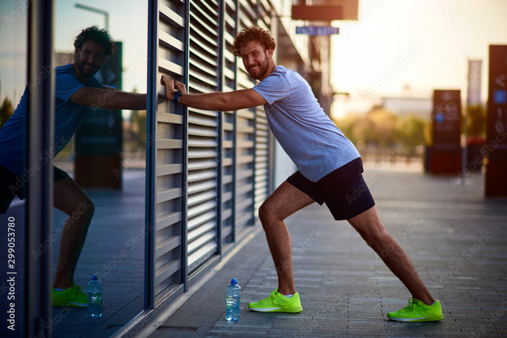 Fototapety, obrazy: Sportsman stretching in urban area during jogging / exercising.