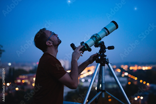 Astronomer with a telescope watching at the stars and Moon with blurred city lights in the background. - 299055504