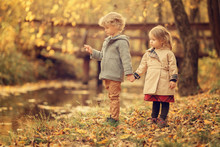 Brother And Sister Holding Hands Standing At The Pond In The Park In Fall Season