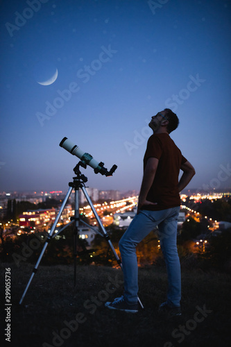 Photo Astronomer with a telescope watching at the stars and Moon with blurred city lights in the background