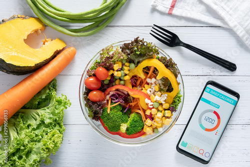 Fototapeta Calories counting , diet , food control and weight loss concept. Calorie counter application on smartphone screen at dining table with salad, fruit juice, bread and vegetable obraz