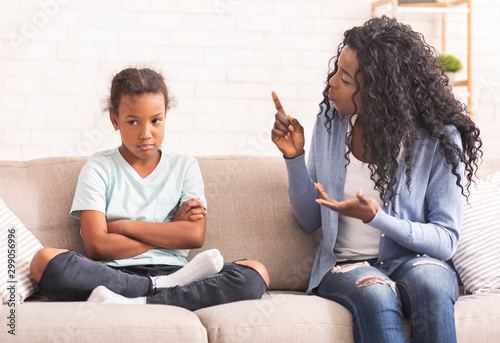 Foto Angry black mom scolding naughty little daughter at home