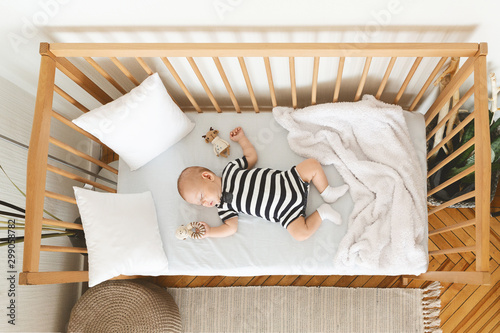 Adorable baby sleeping in crib with toy in his hand Billede på lærred