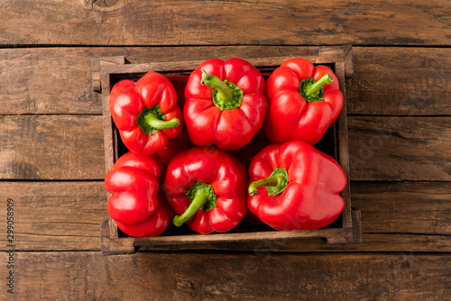 Fotografia Overhead shot of red bell pepper in box on vintage wooden table with copyspace