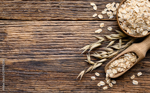 Oat flakes in the bowl with Wooden scoop and oat plant on old wooden table Canvas Print