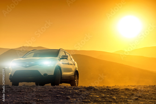 Autocollant pour porte Miel Sunset over mountain landscape with car driving off-road against scenic orange setting sun sky background. Front closeup view of outdoor adventure travel by vehicle in mountains rural land