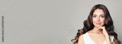 Fototapeta  Cute model woman with long curly hair on banner background