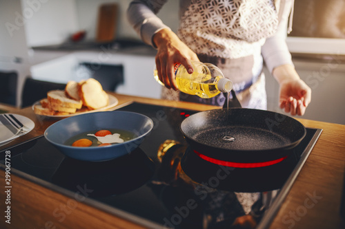 Fototapeta Cropped picture of woman in apron pouring oil in frying pan while standing next to stove. Breakfast preparation concept. obraz