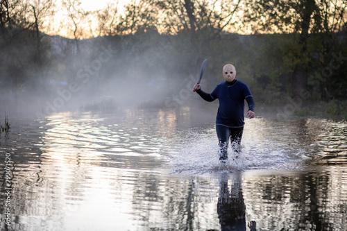 Horror Scene, Maniac or criminal in mask holding knife, walking through a lake a Tapéta, Fotótapéta
