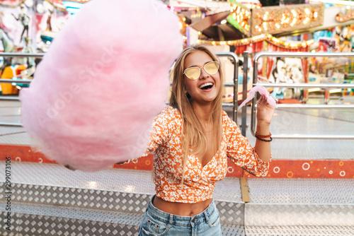 Woman walking outdoors in amusement park eat candyfloss. Fototapet