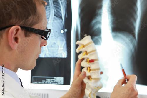 Doctor with  model  of spine watching radiogram  at x-ray film viewer, Canvas Print