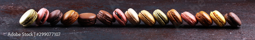 Photographie Sweet and colourful french macaroons or macaron on dark black background, Dessert