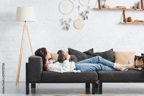 beautiful woman lying on sofa with scottish fold cat in living room Fototapet