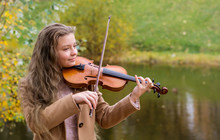 Girl Playing The Violin And Smiling In The Autumn Park At A Lake Background.