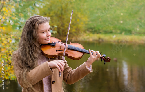 Girl playing the violin and smiling in the autumn park at a lake background Canvas-taulu