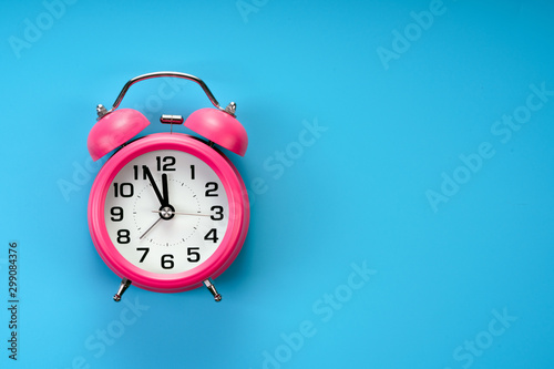 Photo pink rustic alarm clock on blue background