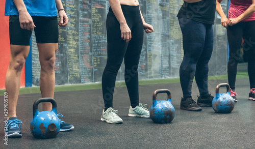 Fotomural  Unrecognizable group of athletes with kettlebells in the gym