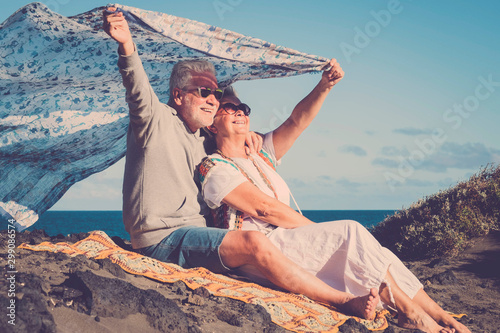 Obraz Happy senior caucasian couple enjoy the outdoor leisure activity together - active old people in love have fun under the sun - ocean and nature in background - fototapety do salonu