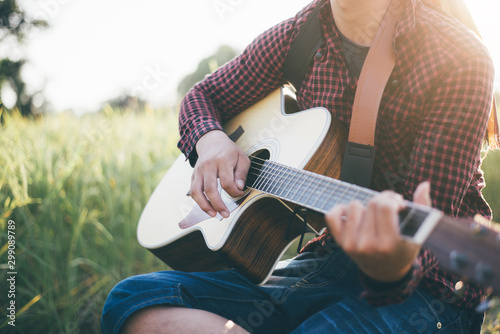 Country music, Man playing acoustic guitar in rice field, Focus on the right hand, Close-up - 299089789