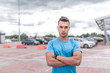 sporty man stands confidently, trainer poses, courageous look confident and strong, training in city during summer, an active lifestyle, modern fitness workout. Free space for motivation text.