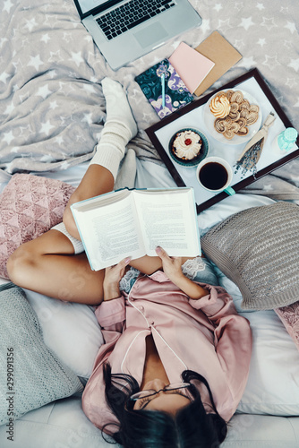 Obraz Top view of beautiful young woman in pajamas reading book and enjoying morning coffee while resting in bed at home - fototapety do salonu