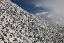 Hill Of Crushed Stone Close-up In The Finished Goods Warehouse Of The Mining Enterprise Against The Background Of A Blue Sky With Clouds. Mining Industry.