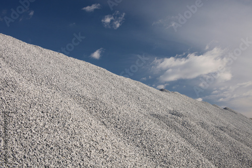 Photo Hill of crushed stone in a mining enterprise against the background of a blue sky with clouds