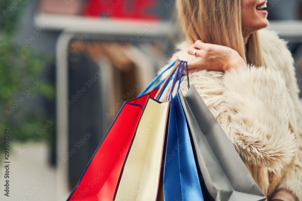 Fototapeta Happy adult woman shopping for clothes in boutique