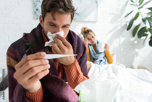 Fotografia sick man with fever holding thermometer and napkin in bedroom with woman behind